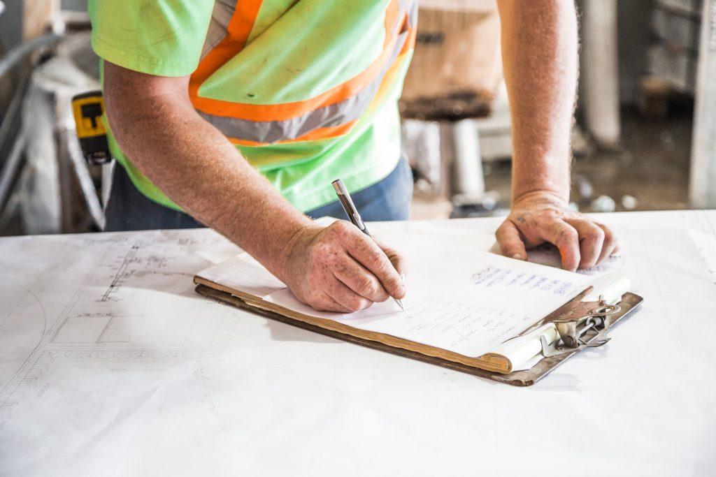 Construction man writing on a clipboard. Hughes Construction.